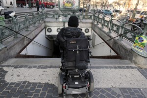 TO GO WITH AFP STORY BY ISABELLE TOURNE - Alain Ansellem, a disable person is pictured on his wheelchair at the entrance of a metro station, on February 19, 2013 in Paris. French Prime Minister Jean-Marc Ayrault received on the first of March 1, 2013 from socialist senator Claire-Lise Campion a report on the accessibility of disabled people. AFP PHOTO KENZO TRIBOUILLARD